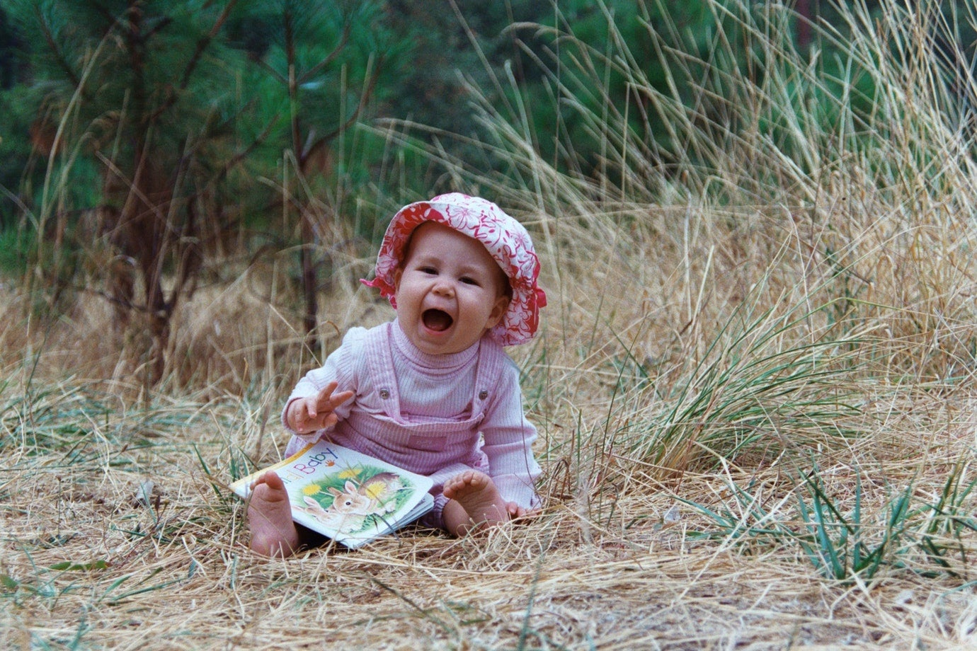baby girl with pink hat and overalls sitting in tall grass and laughing