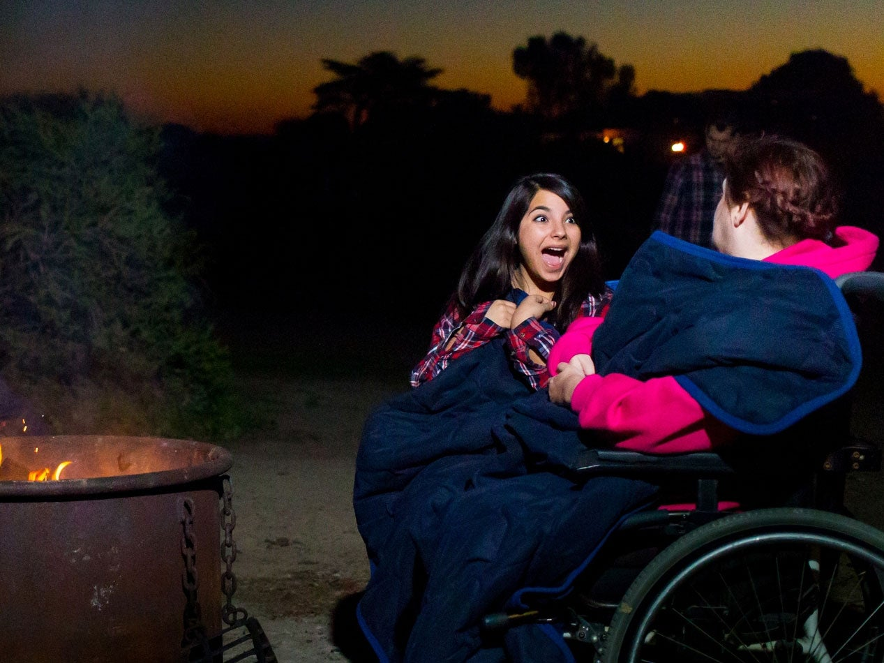 woman faces friend in wheelchair with excited expression on her face as they share a heated blanket in front of campfire
