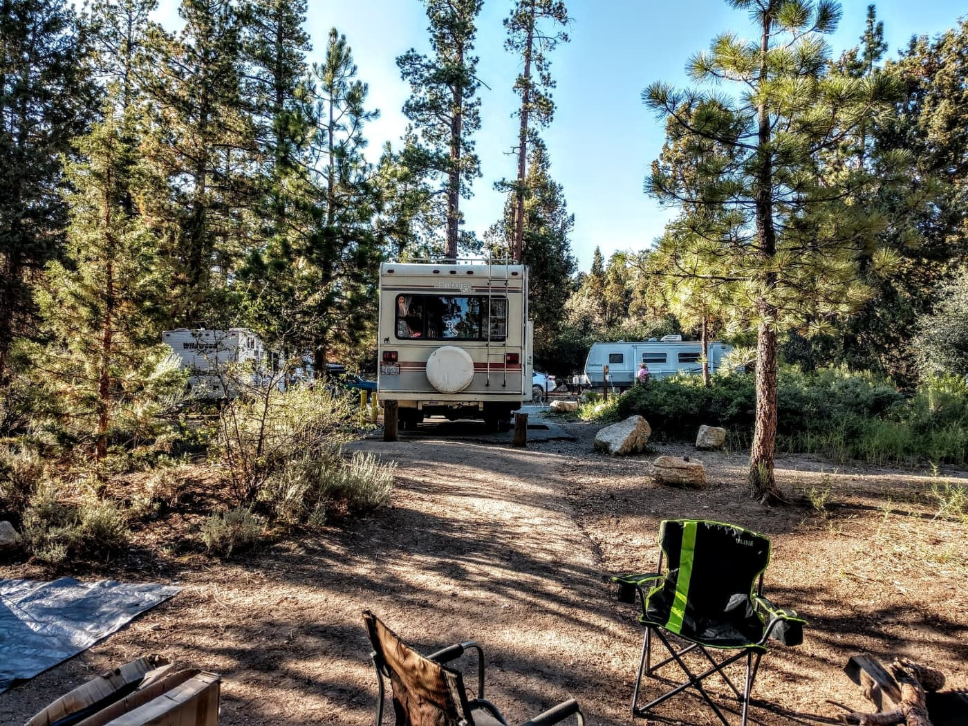 Old School RV from the back parked in a dry bushy area with pine trees and boulders around two other RVs.