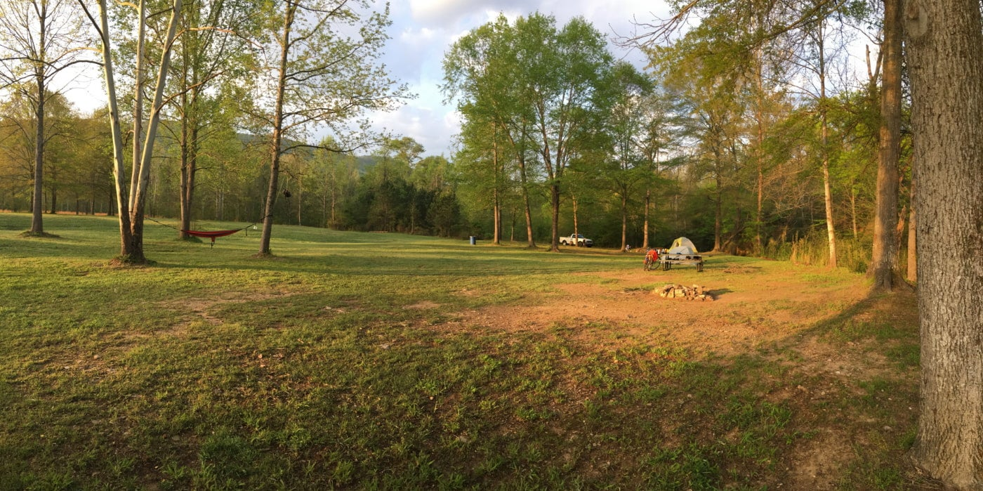 Panoramic image of spacious campsite with tent setup visible in the distance