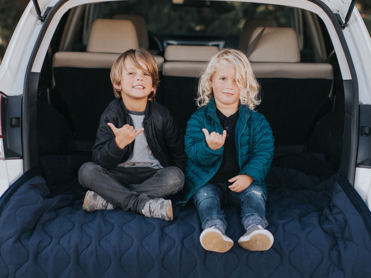 two young boys holding up shaka hand signs in the back of a camping suv