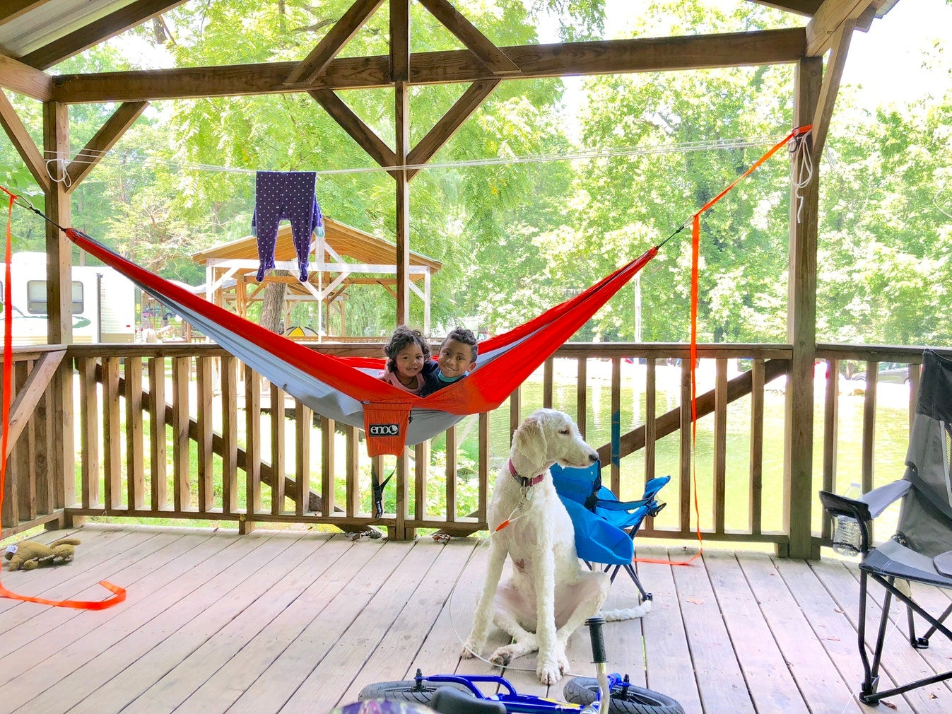 two young children smiling from red hammock hung on deck as white dog sits in the foreground