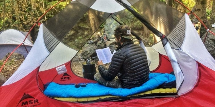 Guy with a brown hat facing away from the camera sitting in a tent reading with a black puffer jacket on a blue sleeping bag on a green sleeping m,at in a red and white MSR tent.