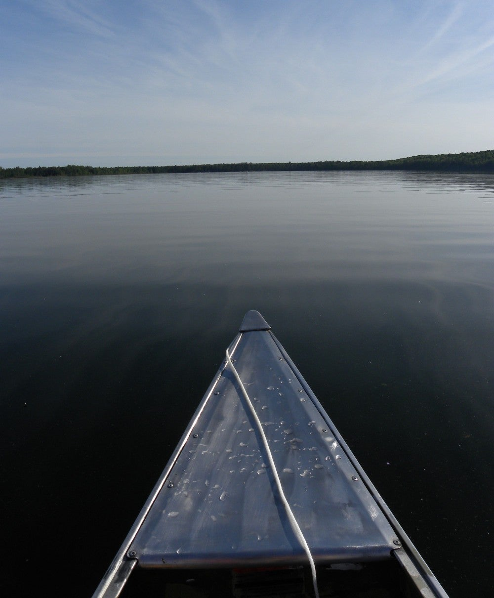 Morning sunlight shining on the bow of a metal canoe in a calm blue lake.