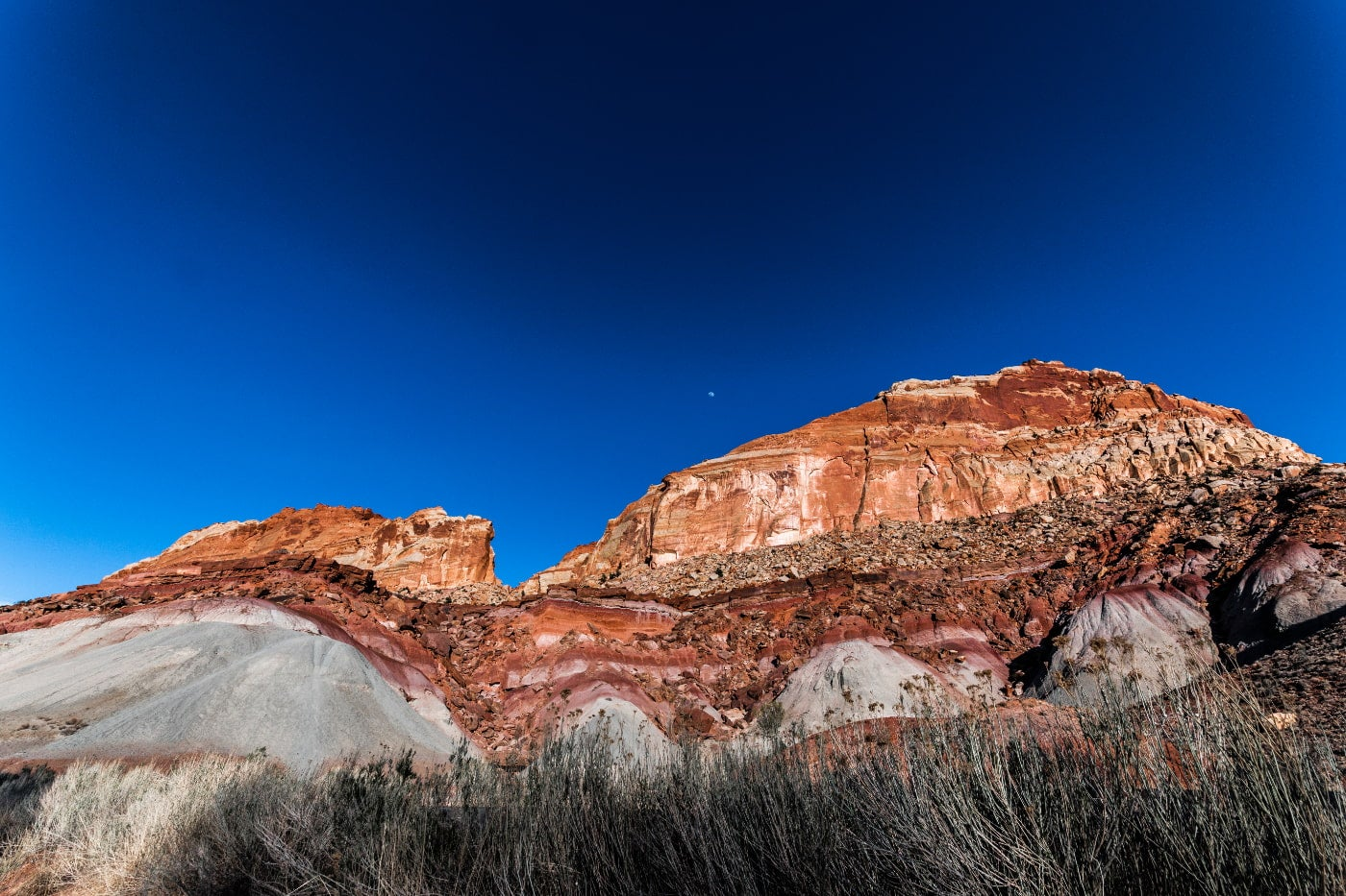 A dark blue sky with a small moon above a large mountain of red striated rock and dead brush beneath it.