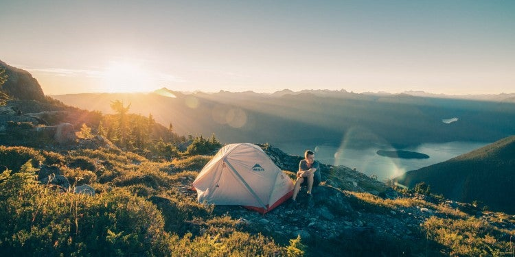 Sun rising behind mountains and streaming into alpine field where guy with white and red tent sits in the brush.