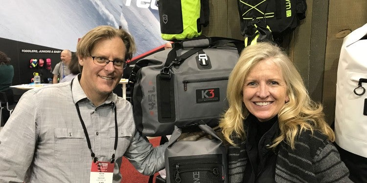 man and woman posing for photo with waterproof duffel bag at outdoor retailer booth
