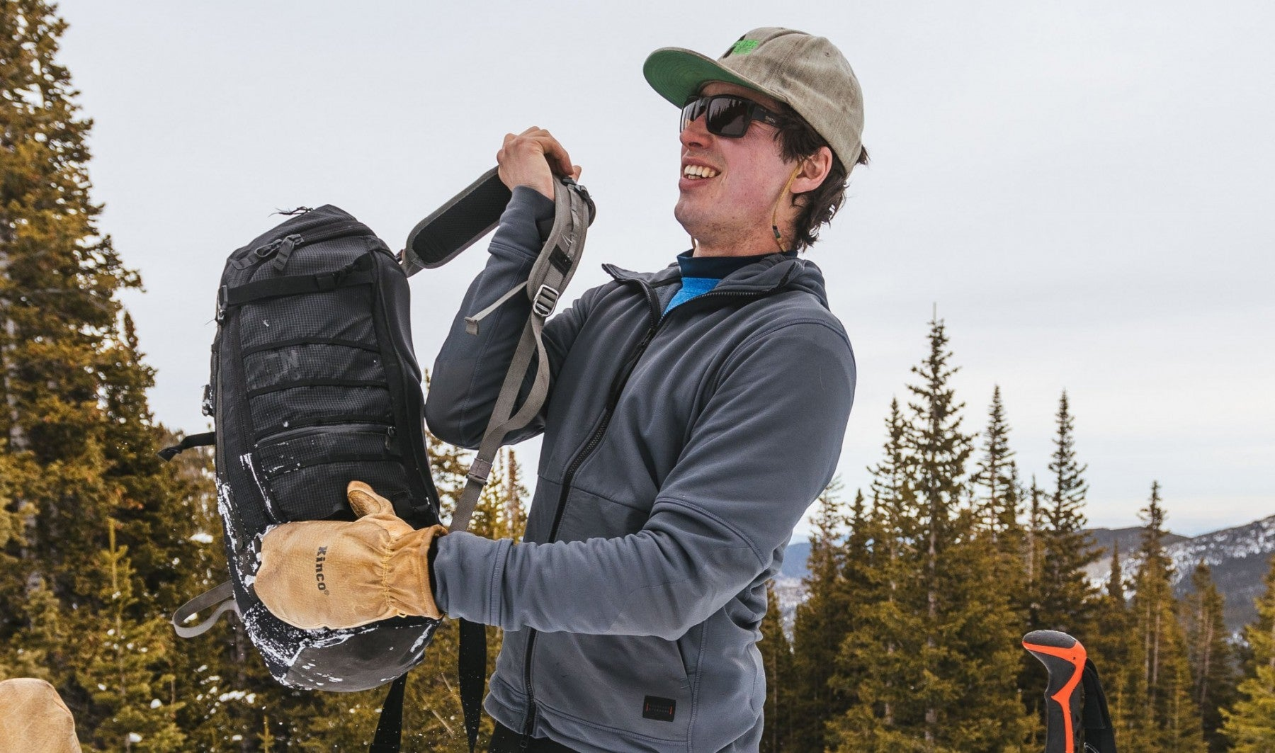 hiker wearing winter gear slings backpack over his shoulder in snowy forest environment