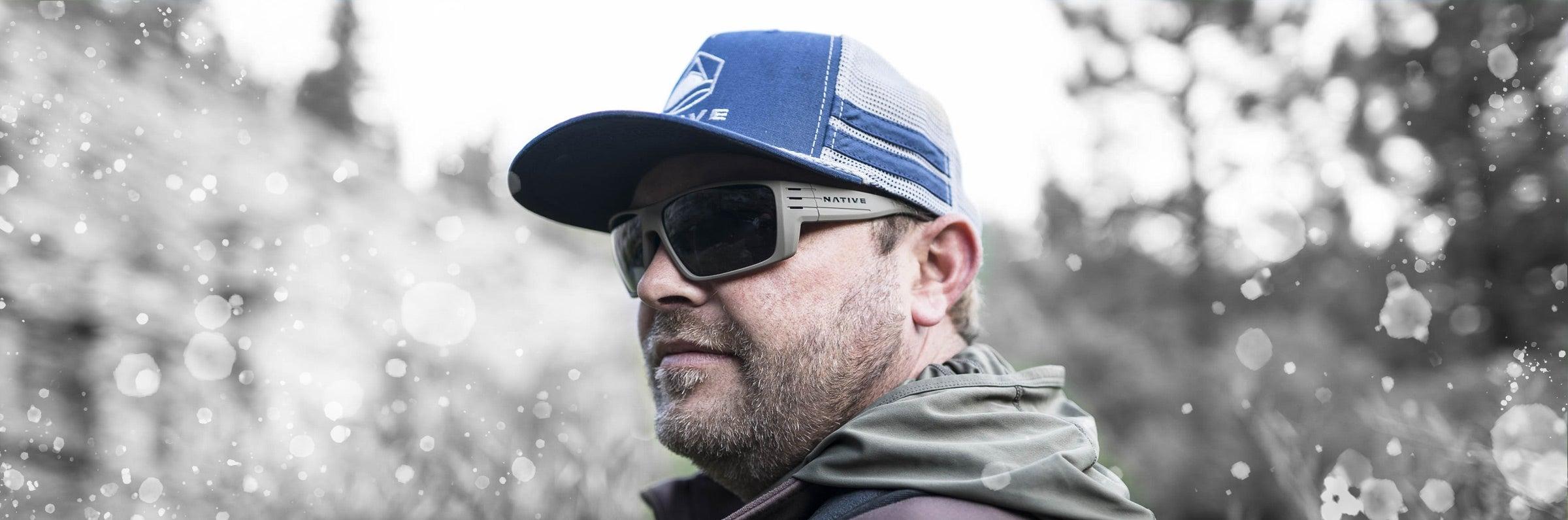 outdoorsman wearing grey native eyewear sunglasses and blue hat