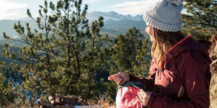 female hiker rests on scenic overlook and holds toiletry bag in hand