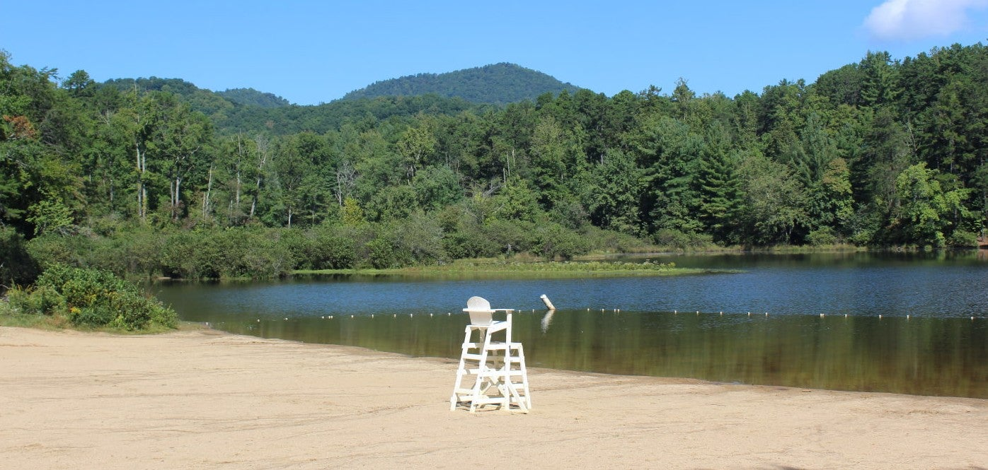 White adirondack-style lifeguard chair on Lake Powhatan shoreline on a sunny day.