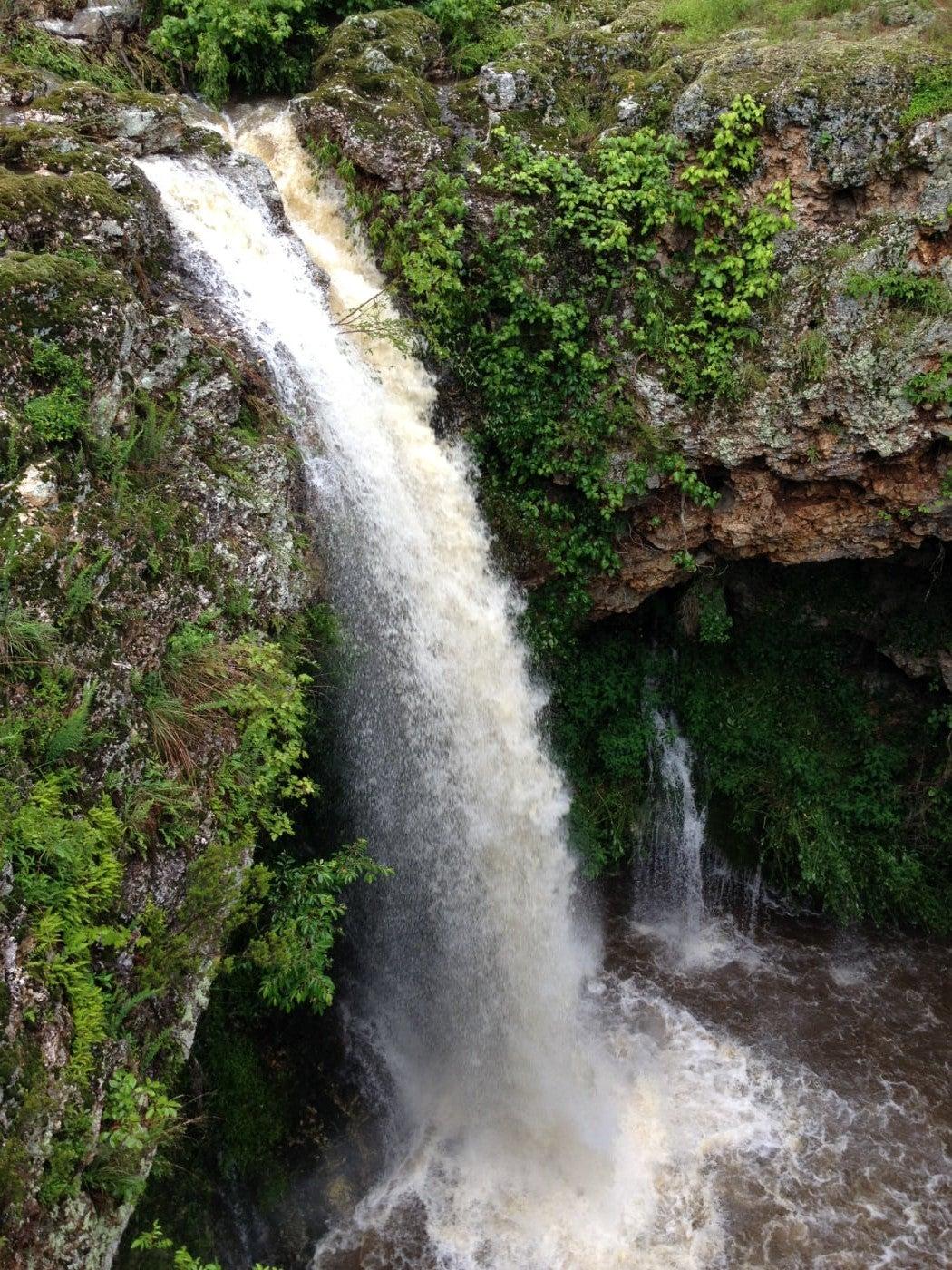 waterfall cascades over green rocky cliffside