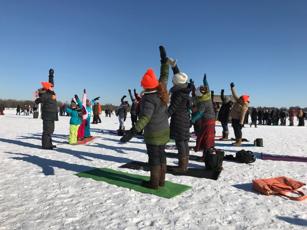 people in winter apparel stretch their right arms over their heads as they participate in outdoor snow yoga