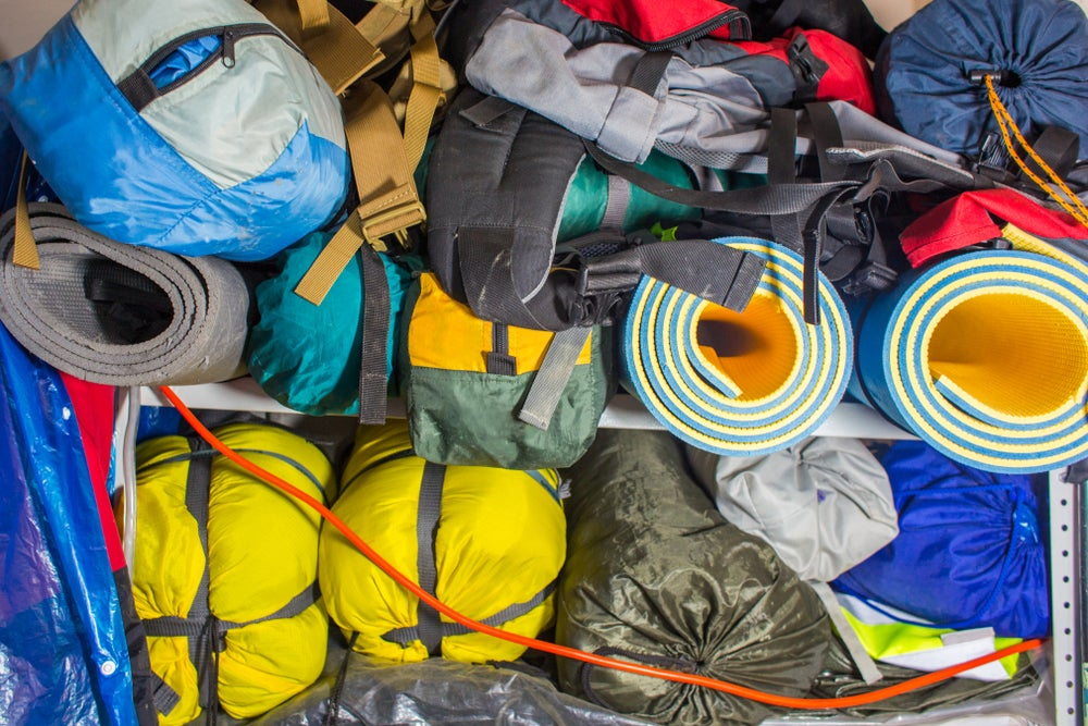 Camping gear including yellow tents, and orange sleeping pad, a black backpack, a green tarp, and more stacked in a large pile.