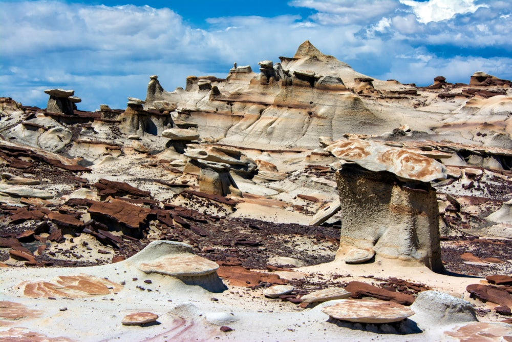 White and dark brown straited rock formations in the Bisti Badlands against a cloudy bright blue sky.