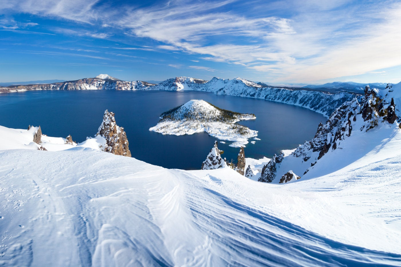 oregon's crater lake surrounded by a heavy layer of snow with Wizard island in the middle of the lake