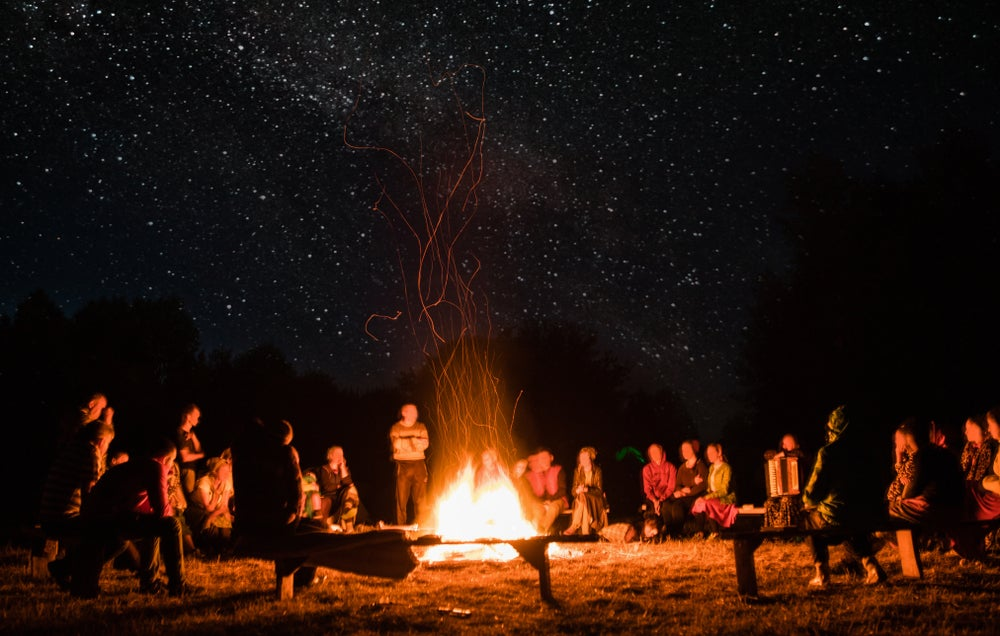 Large group sits on wooden benches around a campfire at night.