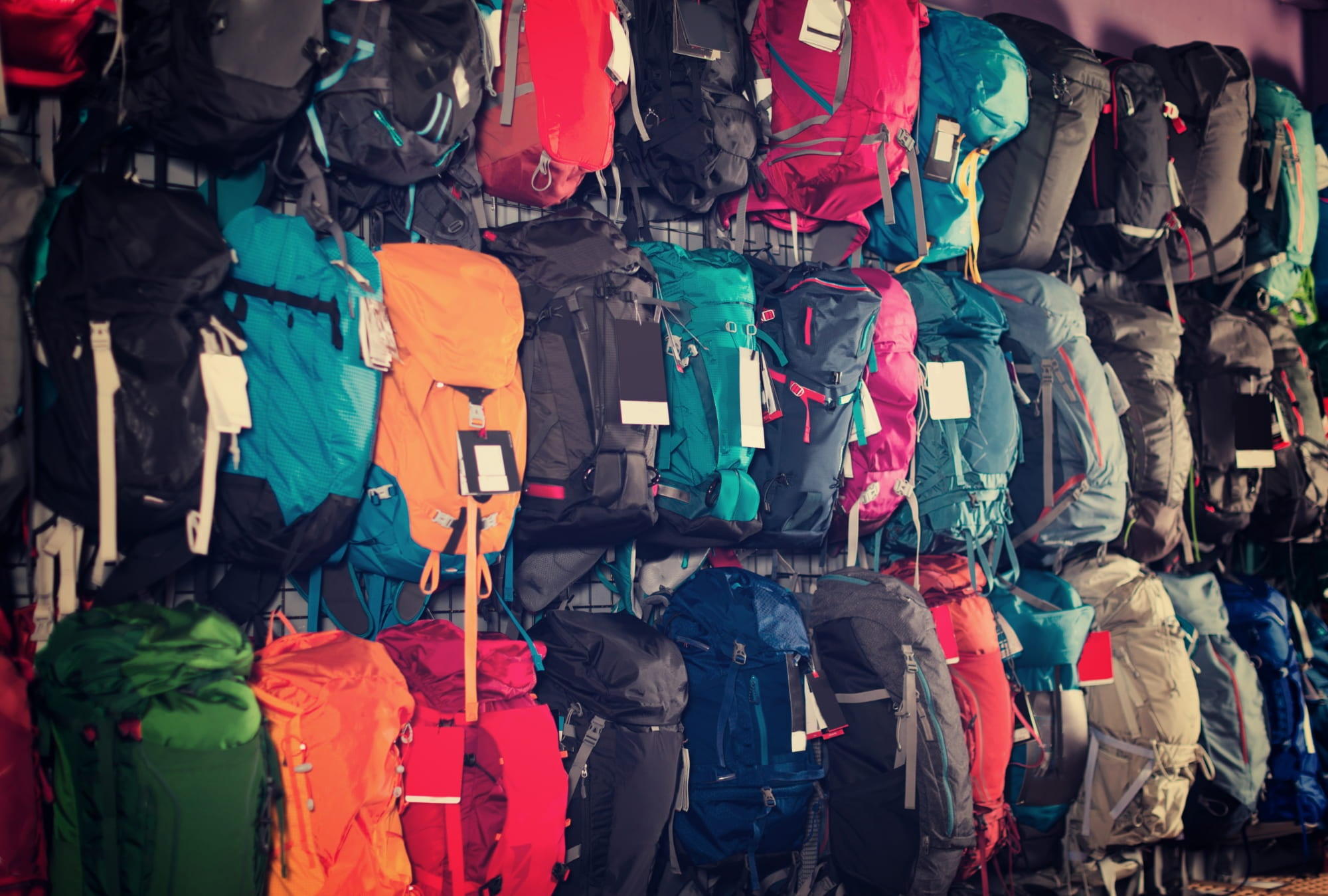 Rows of hanging backpacks in a camping gear rental store