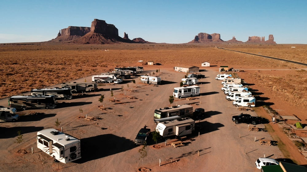 an RV parking lot full of RVs in a desert setting with rocky buttes in the background