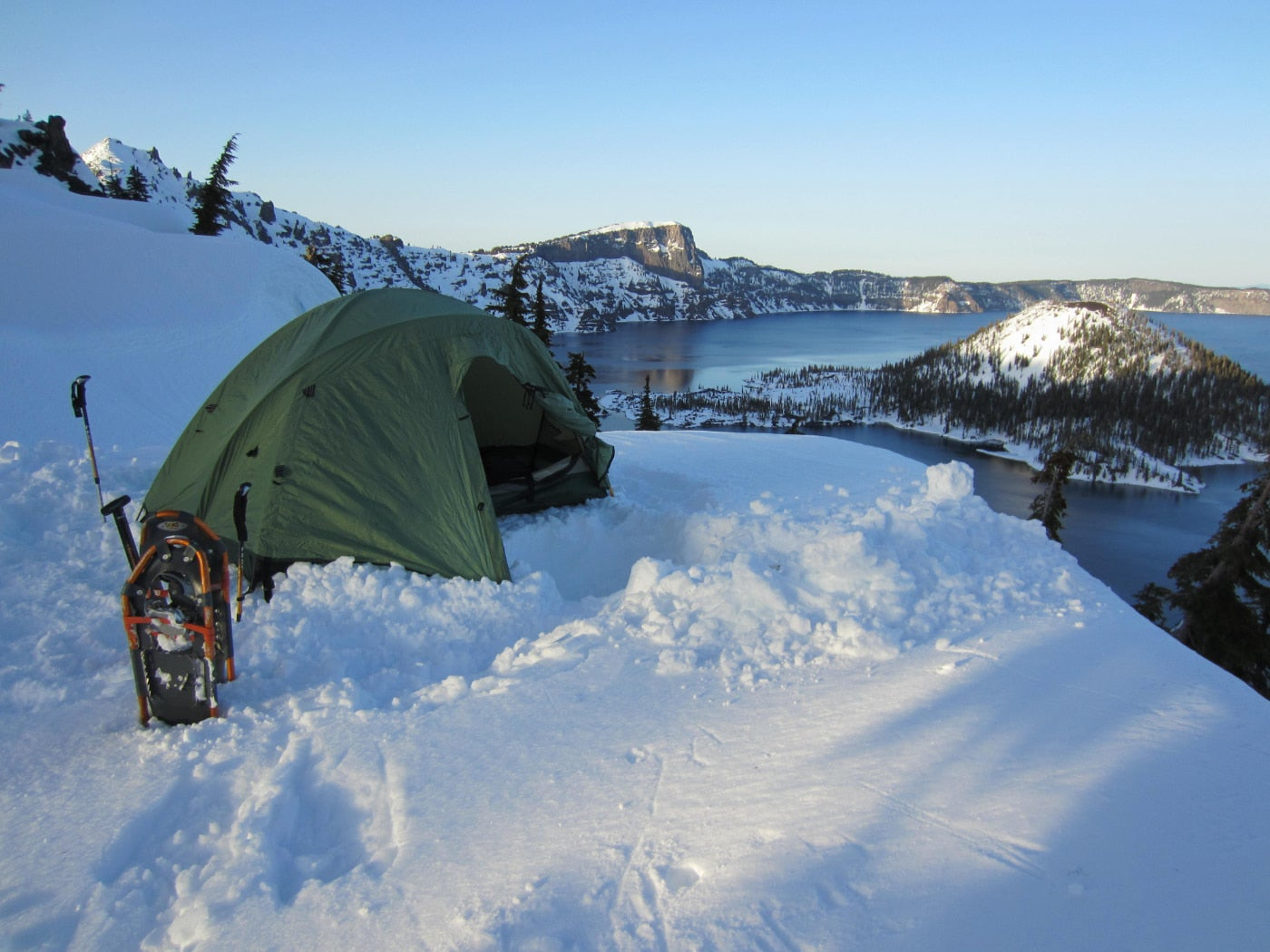 Orange snowshoes and a green tent sit in the deep snow beside crater lake in winter.