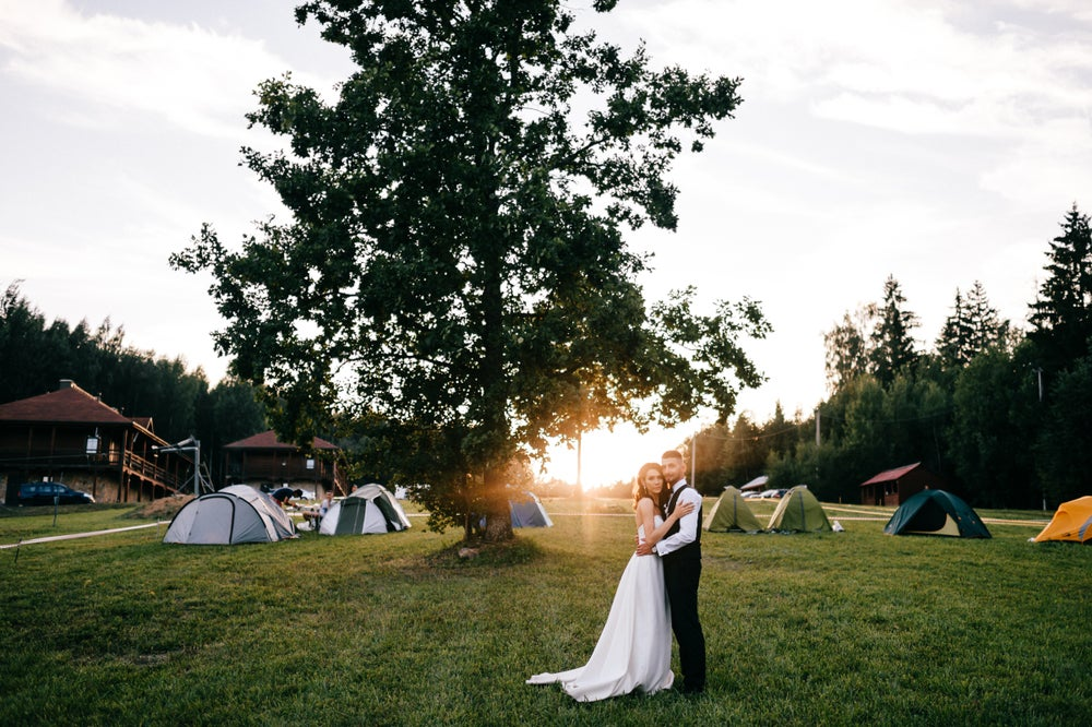 Couple stands together in formal wedding attire, in front of large trees, a lodge building, and a cluster of dispersed tents.