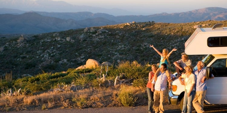 Multi-generational family gathered around the front of an RV during a sunset overlooking hills and mountains