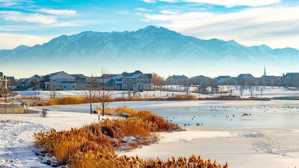 A suburban Salt Lake neighborhood on a frozen lake in winter surrounded by a foggy inversion with mountains in the background.