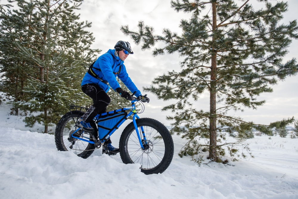 Winter cyclist on a fat bike passes trees as he rides downhill through the snow