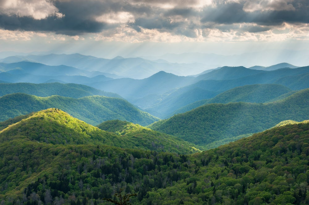 sun rays shine through clouds onto blue ridge mountains