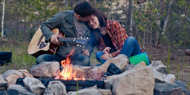 a couple leans on each other by a fire while one of them holds a guitar