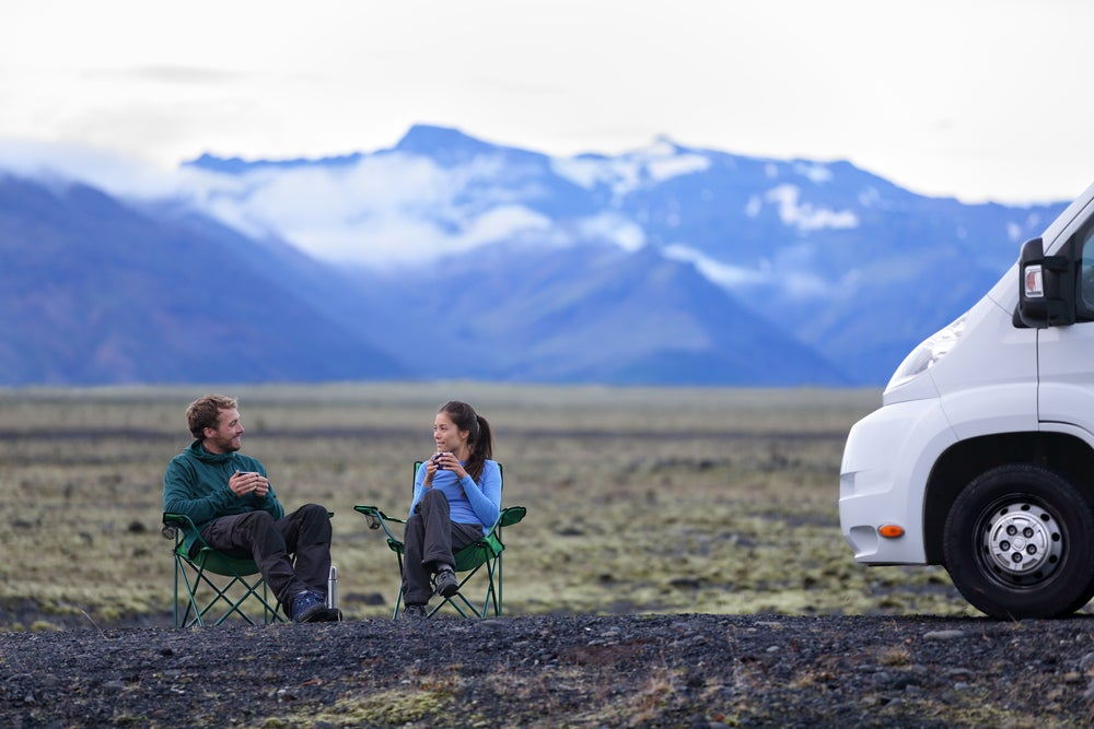 Couple sits in cozy sweaters in camp chairs in a field beside their RV drinking coffee.