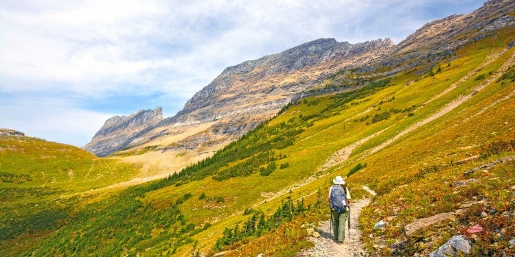a hiker walks up a rocky trail in glacier national park in montana