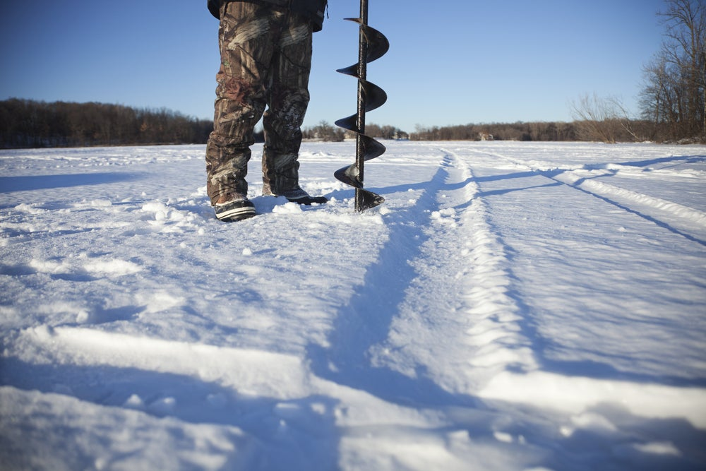ground level view of man in winter gear preparing to drill ice fishing hole