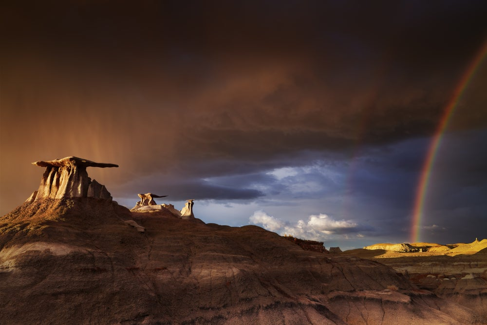 wide angle view of the bisti badlands seen below rolling storm clouds and a vibrant rainbow