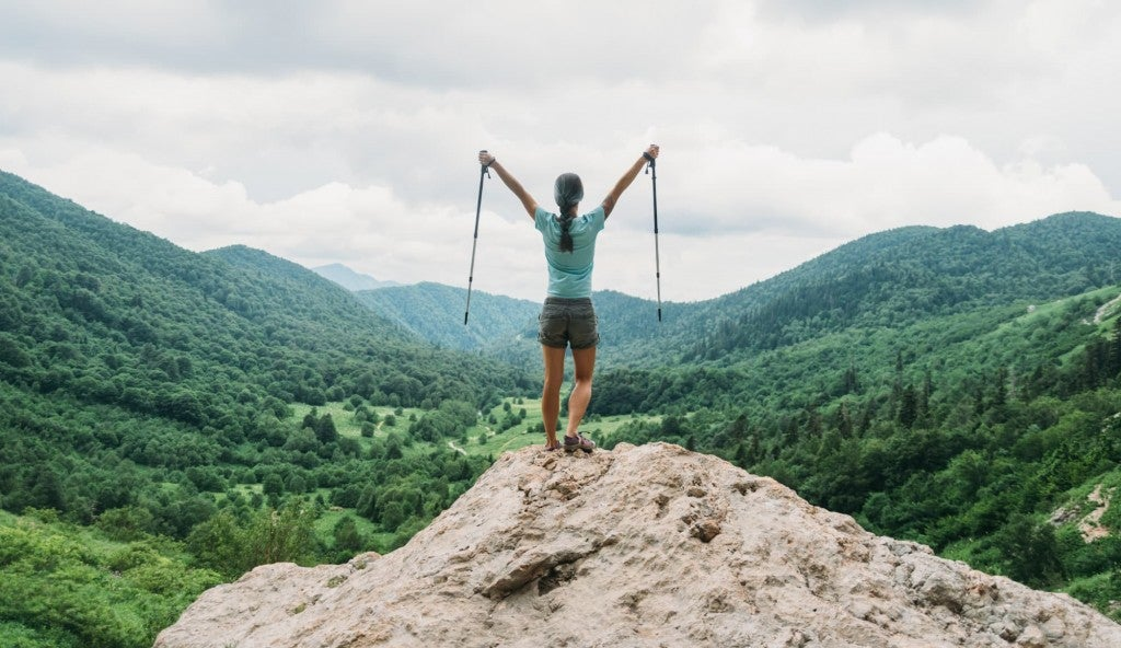 a woman holds collapsible trekking poles at the top of a rocky cliff overlooking a lush mountain range