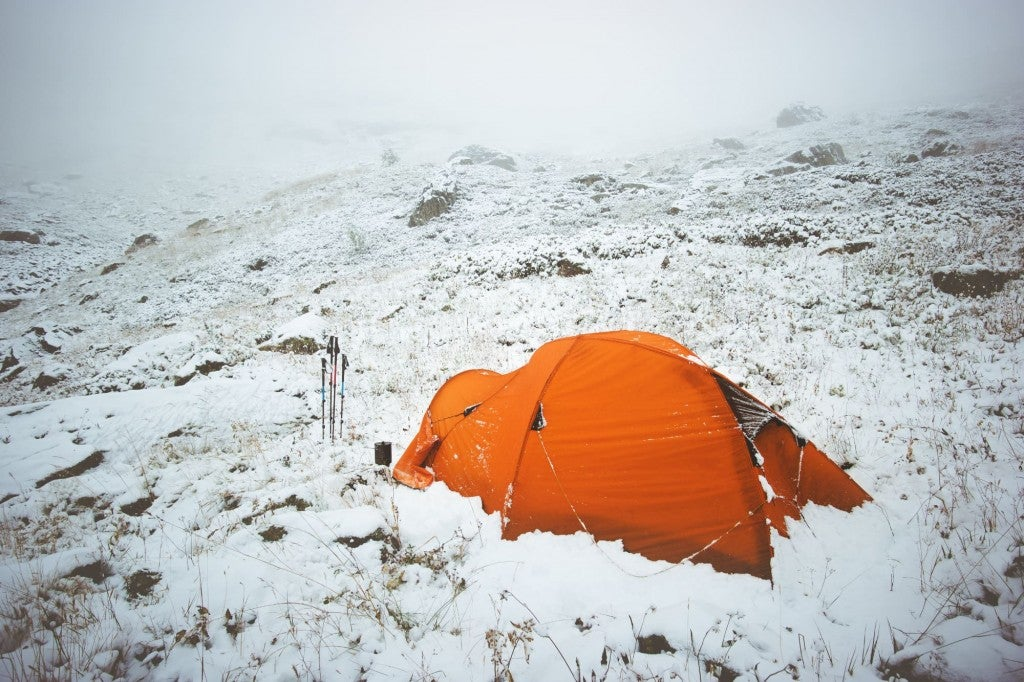 an orange tent rests on a snowy field in the middle of winter