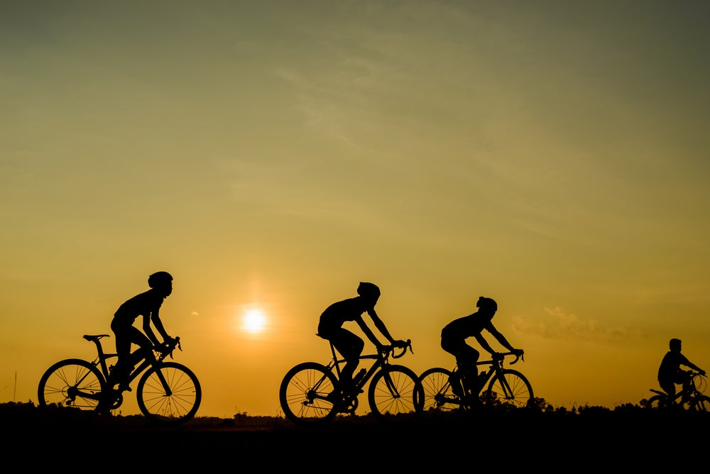 four silhouettes of cyclists ride on a flat plain while the sun sets behind them