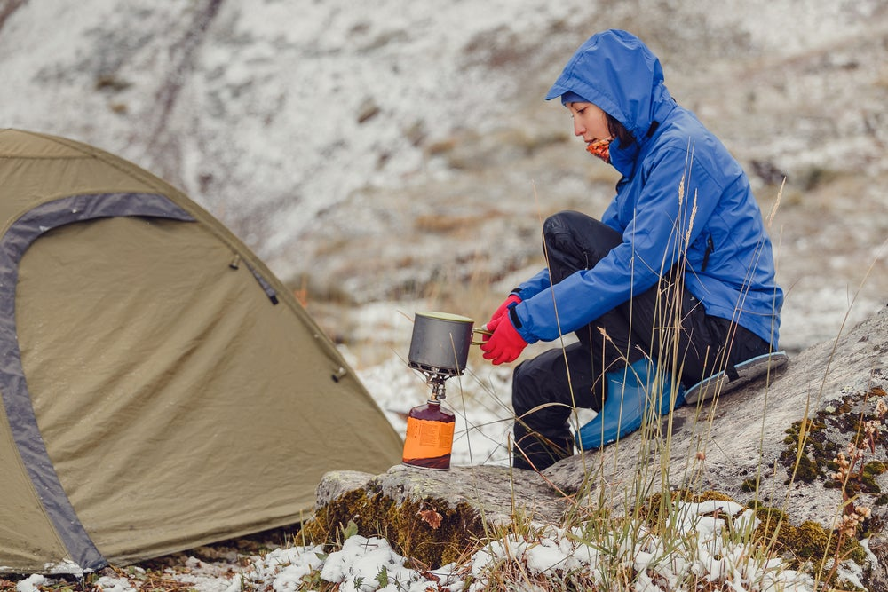 Woman in a blue hooded rain coat holds pot over a gas fire while winter tent camping