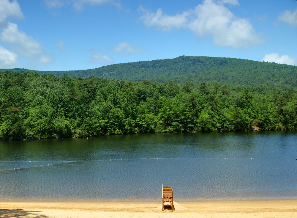 a lakeshore beach with a lifeguard chair at Hanging Rock State Park Lake, with rolling green woodlands in the background