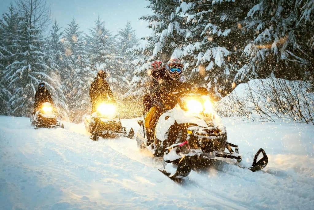 three snowmobilers travel a snowy trail with headlights on at night