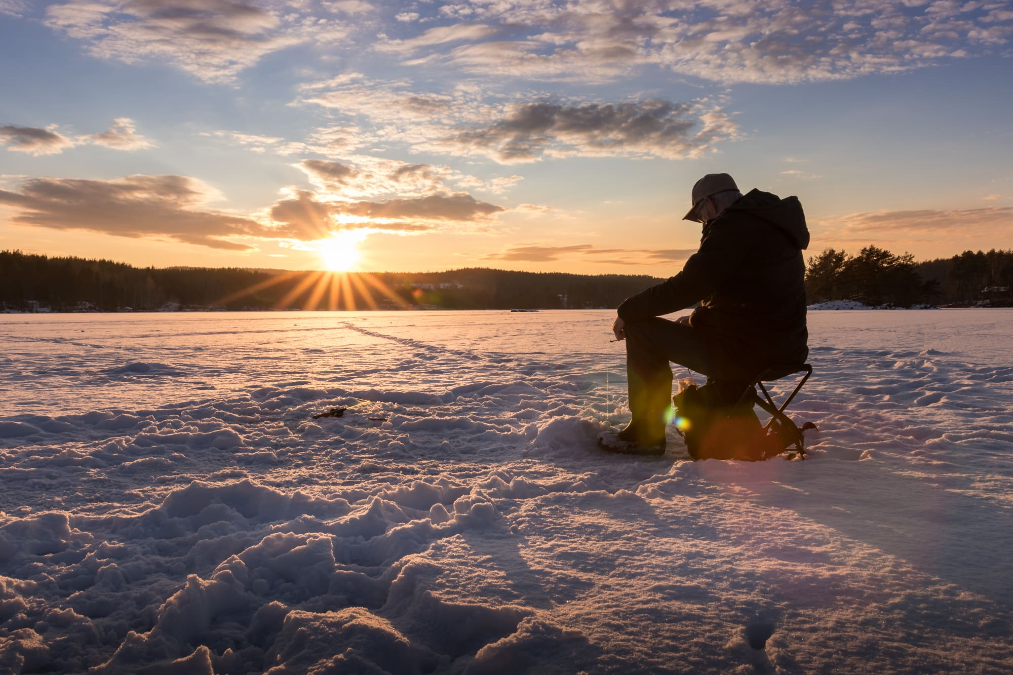 a silhouette of a person sits on a frozen lake while ice fishing in minnesota