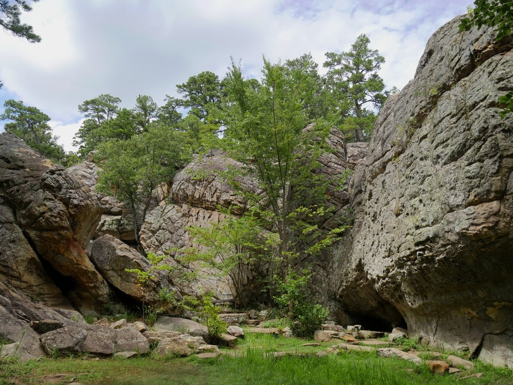 Landscape of large cliffs faces and trees in Robbers Cave State Park.