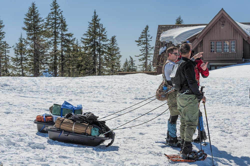 snowshoers towing gear on a sled stop for directions in front of crater lake lodge