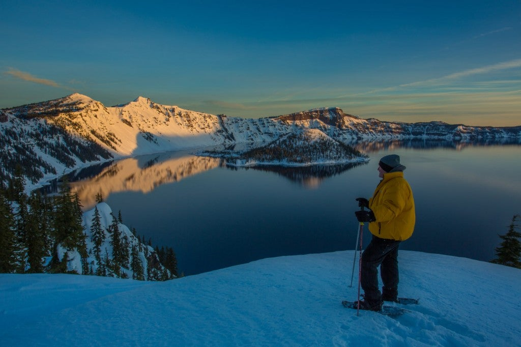 a man at a snowy overlook snowshoeing in crater lake national park at sunset