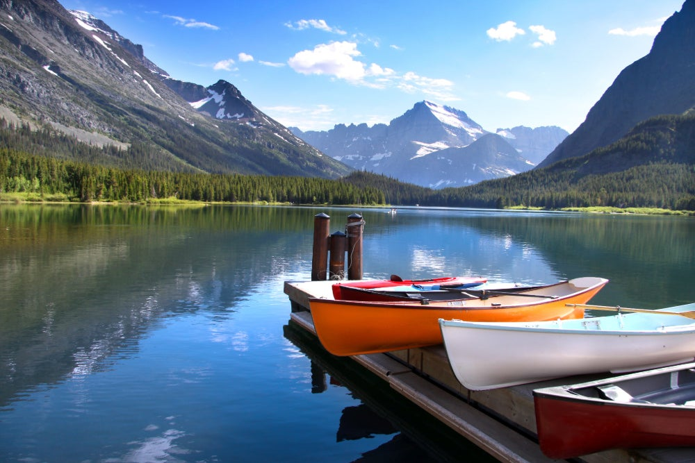 three canoes docked on a pier on lake mcdonald at glacier national park