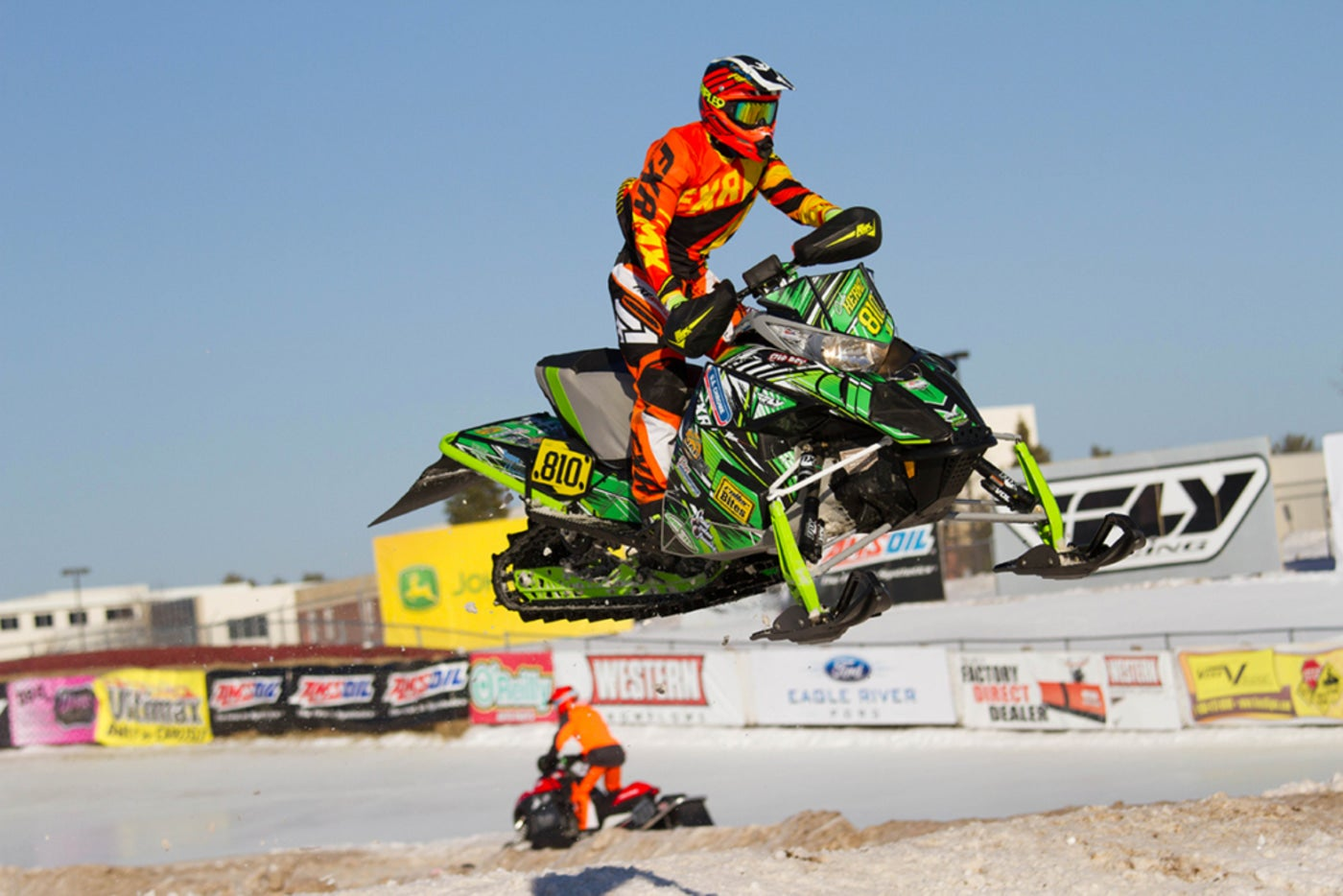 professional snowmobiler in full gear jumping a hill at a derby