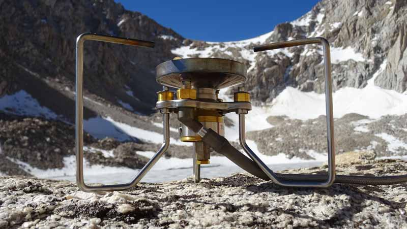 close up of soto outdoors multi fuel stove in snowy mountain landscape