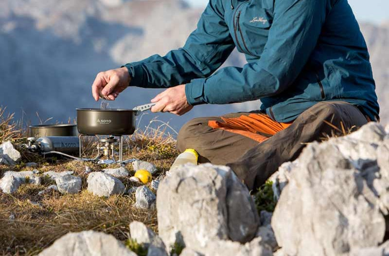backpacker making a meal on a soto stove in the mountains