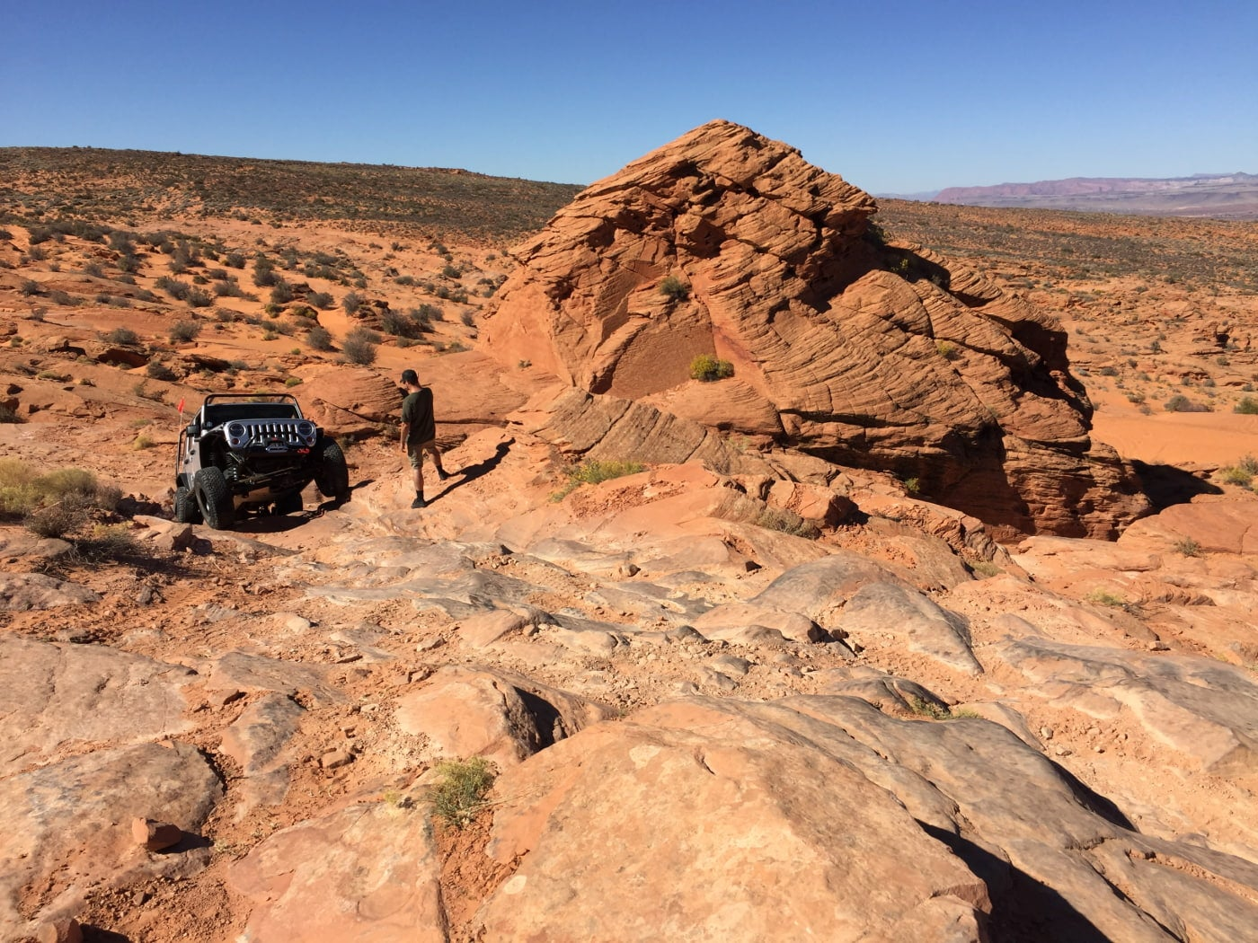 A man stares at a Jeep car in a large and flat red rock desert of southern Utah near a rocky outcropping