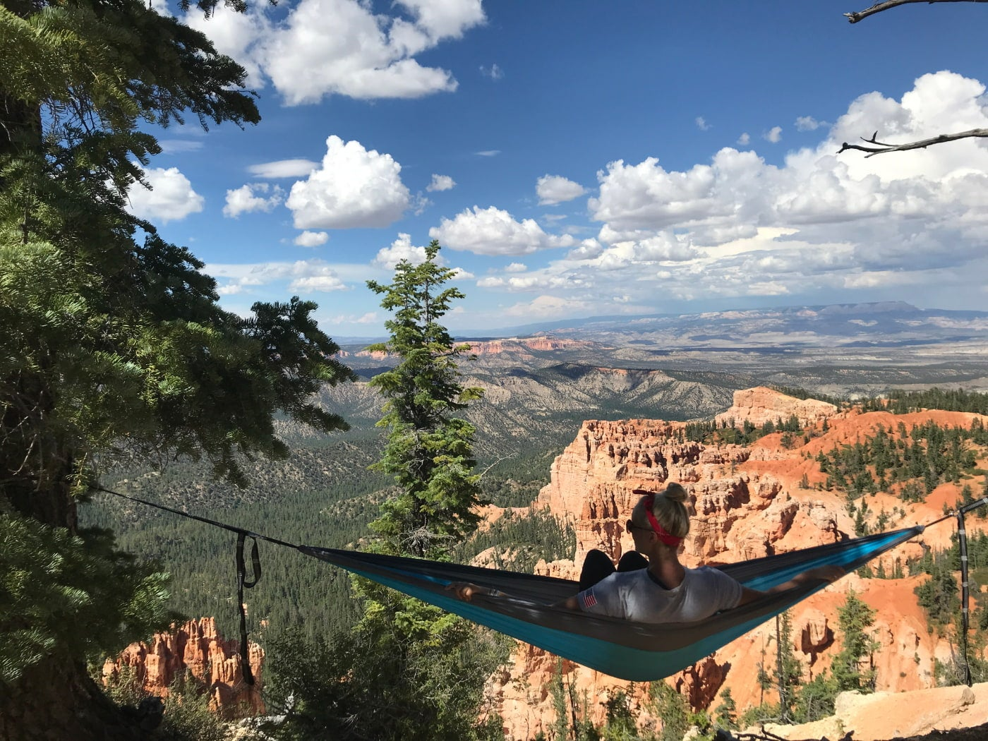 Women with grey shirt and blond hair in a bun sits in a blue hammock facing a panoramic overlook of the Bryce Canyon from above